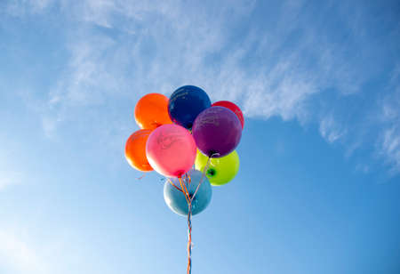 Bright balloons with the inscription in Russian Happy Birthday on the background of a bright blue sky. Festive background.