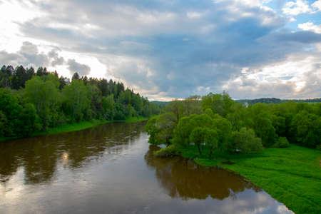 Summer landscape. A dark river flows among green banks under a dark, cloudy sky. Archivio Fotografico