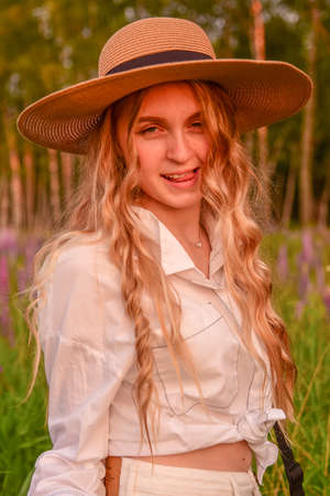 A flirtatious beautiful teenage girl with long blonde hair, wearing a straw hat and white clothes, poses against a background of blooming lupines. Photo session in nature.