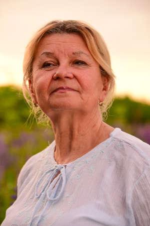 Portrait of an elderly woman against the  lupine field