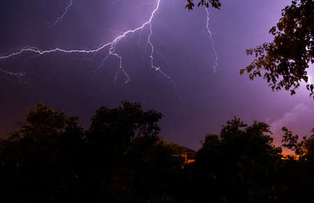 Lightning strikes between blue stormy clouds above a residential area. Archivio Fotografico
