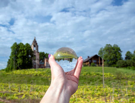 Glass ball in a woman's hand with a bright manicure. The old dilapidated Church is reflected in the lens.