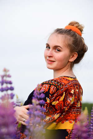 A beautiful young girl with blonde hair tied in a bun, in an ethnic dress, posing against a background of blooming lupines. Photo session in nature.