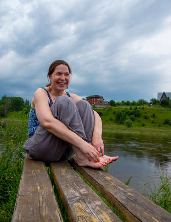 A middle-aged woman sits on a wooden bench on the river Bank on a cloudy summer day.
