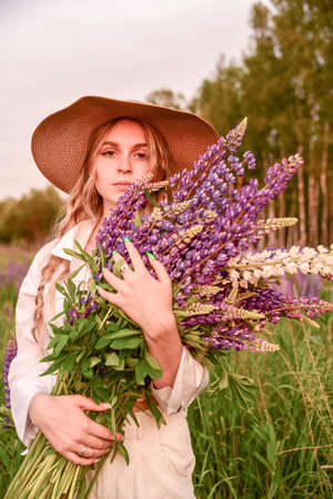 A young beautiful girl in a white shirt and a wide-brimmed straw hat with a bouquet of flowers poses in a Lupine field.