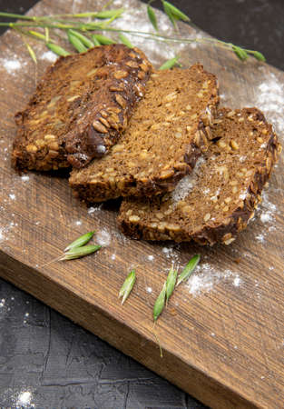Fitness bread with seeds, cut into pieces, lies on a wooden Board. Archivio Fotografico
