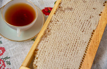 Honey combs and a Cup of tea on a linen tablecloth. Photographed from above, the concept of healthy eating.
