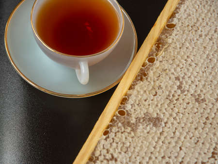 Honey combs and a Cup of tea on a smooth black surface. Photographed from above, the concept of healthy eating.