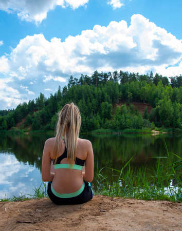 A girl with long blond hair in a sports top sits on the lake with her back to the camera.
