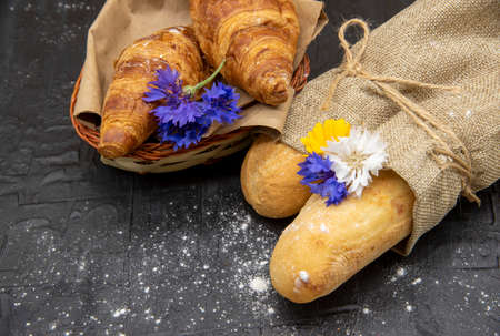 Baguettes wrapped in coarse linen and a basket of croissants decorated with flowers on a black slate background.