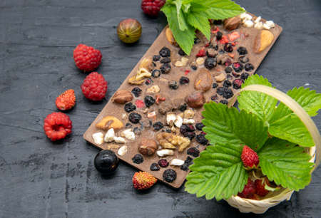 Chocolate bars, various ripe berries and mint leaves lie on a black slate background. Advertising of confectionery, copy space for text.
