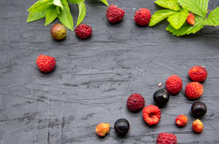 Ripe fresh berries and mint leaves lie on a black slate background. Copy space for text, design.