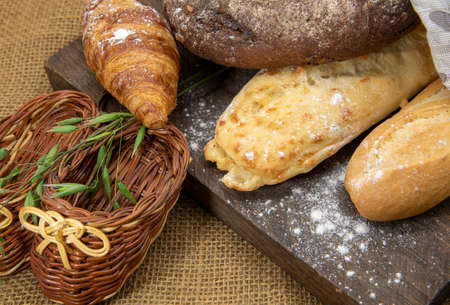 Several types of bread lie on a rough wooden Board against the background of matting. Advertising bakery products, copy space for text. Archivio Fotografico