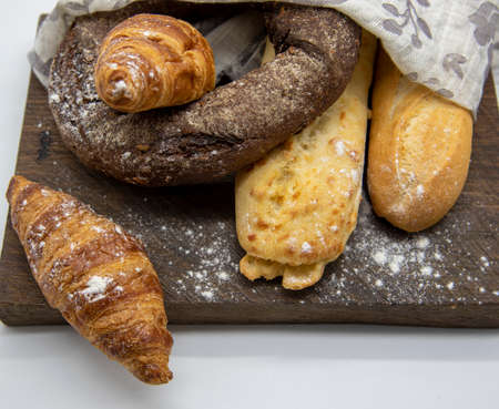 Several types of bread lie on a rough wooden Board on light background. Advertising bakery products, copy space for text.