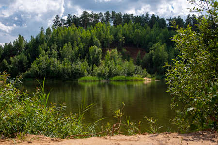 The lake is surrounded by green forests. Trees reflect in the water and turn it green. Summer landscape. 版權商用圖片