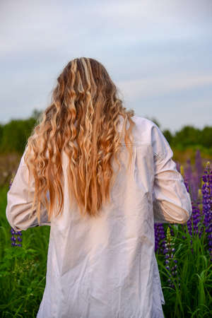 A girl with long blond hair in a white shirt stands with her back to the camera against a lupine field.