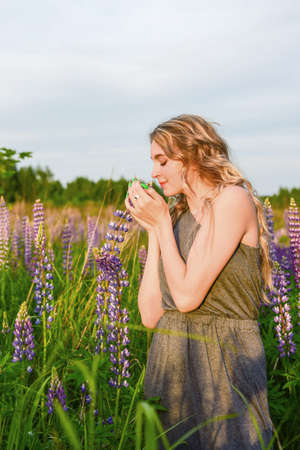 A blonde girl with long wavy hair in an elegant gray dress with an open shoulder poses in lupine fields.