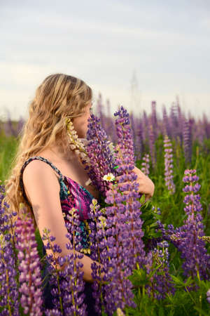A charming blonde girl with long wavy hair poses in a field with bright lupines. Archivio Fotografico