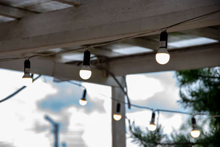 A garland of burning light bulbs hangs under the wooden ceiling of the summer porch.