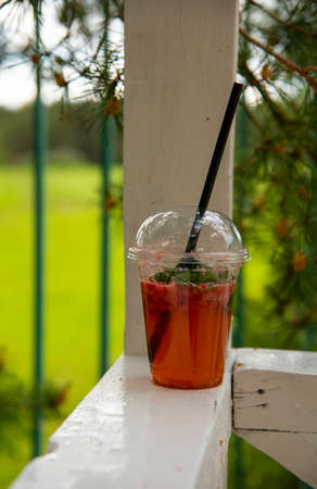 A single-use plastic glass with a refreshing drink stands on a wooden crossbar.