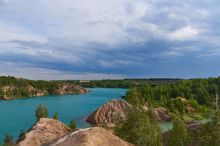 Blue lake among the sand hills on the textured background of the cloudy sky. Archivio Fotografico