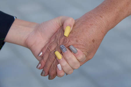 The hand of a young girl holding the hand of an elderly woman.