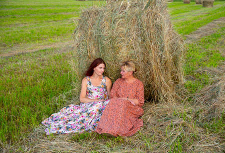 Two women, a mother and daughter, in bright dresses, sit side by side, leaning against a haystack. Foto de archivo