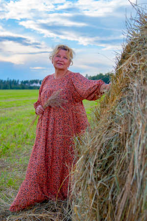 An elderly woman with blond hair in a long country dress poses in haystacks. 免版税图像