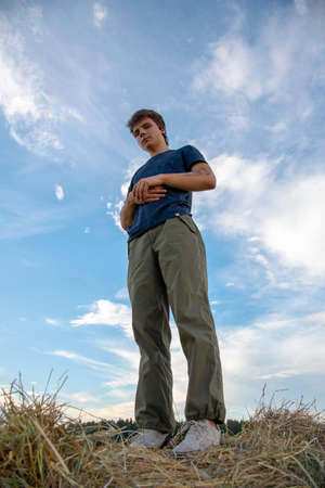 A young man stands on a haystack against a blue cloudy sky and looks at the camera.