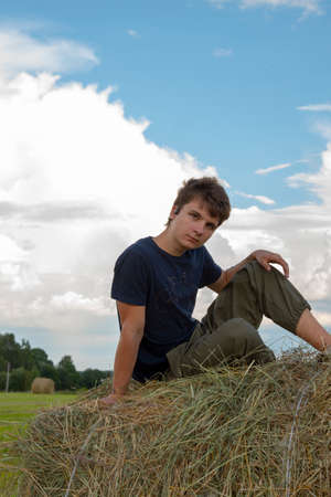 A handsome young man is sitting on a haystack in the fields against a blue cloudy sky. Banque d'images