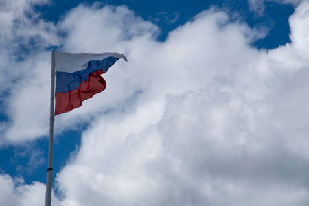 Russian tricolor flag waving in the wind against a cloudy sky.Horizontal photo.