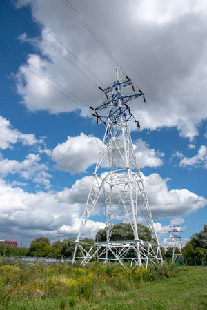 Power line. A pole with high-voltage wires against a bright blue sky. Stockfoto