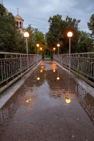 A small pedestrian bridge illuminated by lanterns. Lights are reflected in puddles.