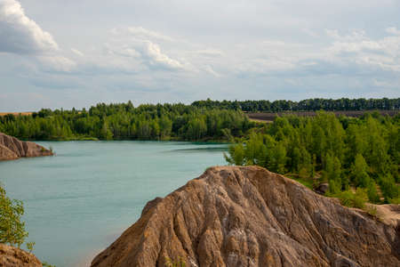 Bright summer landscape. Blue lake among the sand hills on the textured background of the cloudy sky. Stockfoto