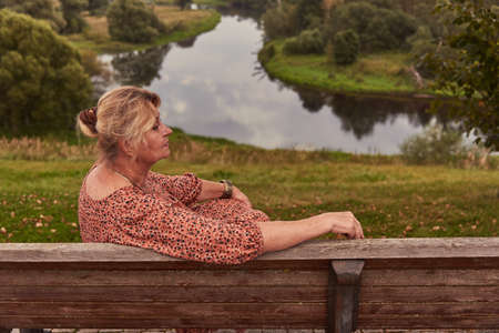 A woman aged 65 is sitting on a wooden bench on a high Bank and admiring the river.