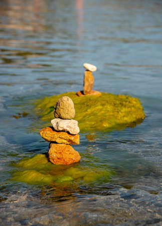 Textured stones, stacked in a pyramid, against the background of clear sea water. Copy space for text, design.