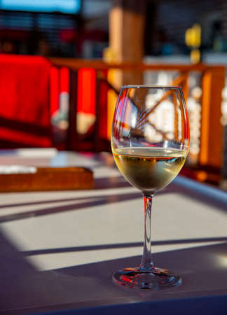 A glass of cool white wine on the bar on a bright abstract background. Stockfoto