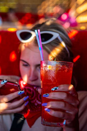 The girl is holding a glass with a bright cocktail and a red phone. The sun shines through the window bars. The focus is on a glass with a drink. Stockfoto