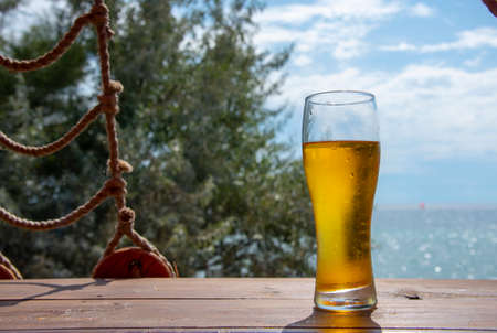 A steaming glass of beer stands on the bar against the backdrop of the seascape.
