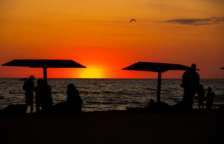 Black silhouettes of people and beach umbrellas against a bright, almost red, sunset. Stockfoto