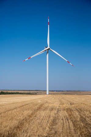 One windmill stands in a mown field against a clear blue sky.