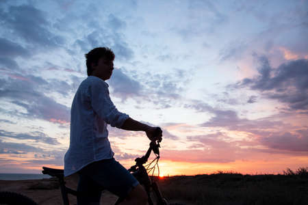 Silhouette of a young man with a Bicycle against the background of a bright colorful sunset. Stockfoto