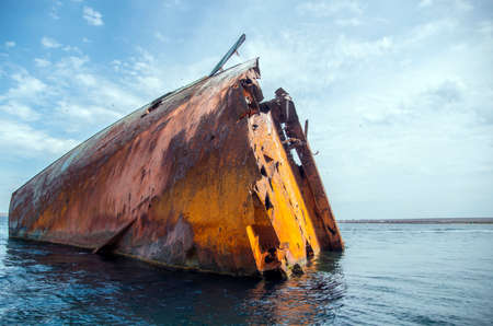 The rusty remains of a sunken ship sticking out of the sea water.