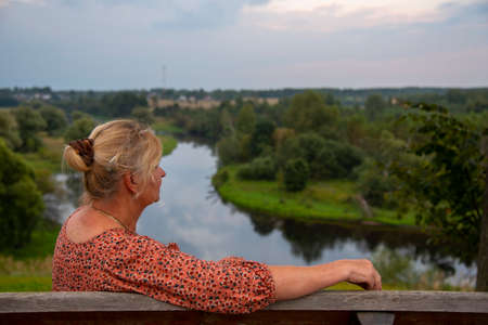 An elderly 65-year-old woman sits alone on a bench on a high Bank above the river with her back to the camera. Stockfoto
