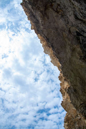 Textured rock against a cloudy blue sky. Natural background. Copy space for text, design. Stockfoto