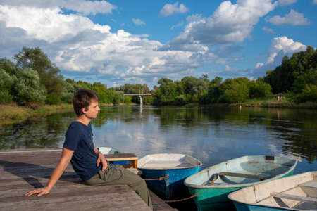 A young man sits on a boat dock on a bright summer day.
