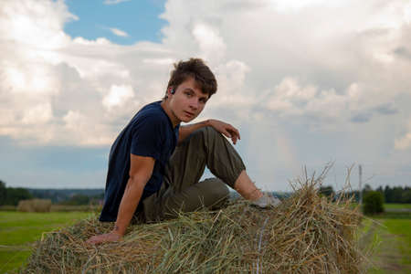 A handsome young man is sitting on a haystack in the fields against a blue cloudy sky. Stockfoto