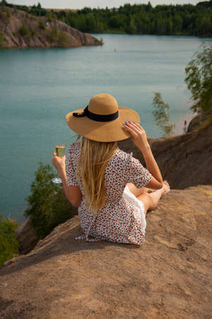 A blonde girl in a straw hat and summer dress is sitting with a glass of champagne on a high hill above the lake.