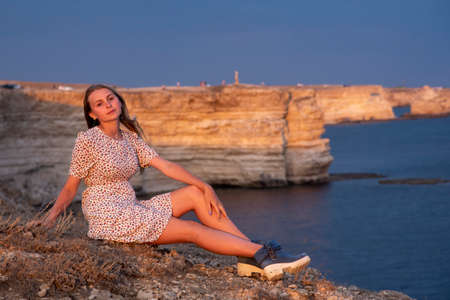 A beautiful girl is sitting on a rock above the sea, illuminated by the setting sun.