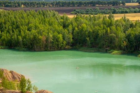 Top view of the green lake surrounded by trees. Summer Sunny landscape.